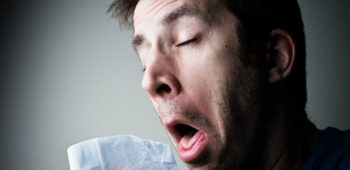 A man sneezing into a hanky