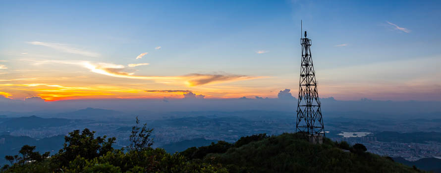 A photograph of a communications antenna with sunset in the background