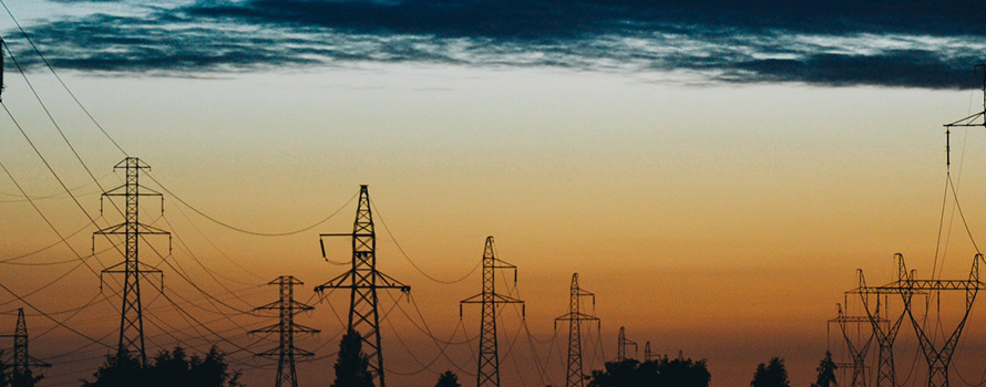 A sunrise behind a line of high voltage towers or pylons