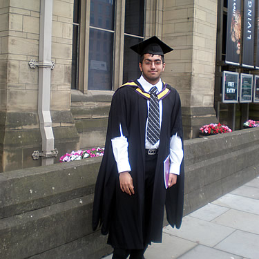 Adil after his graduation ceremony, standing outside Manchester Museum.