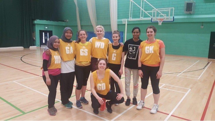 Amy stood with a netball team, wearing bibs with positions on
