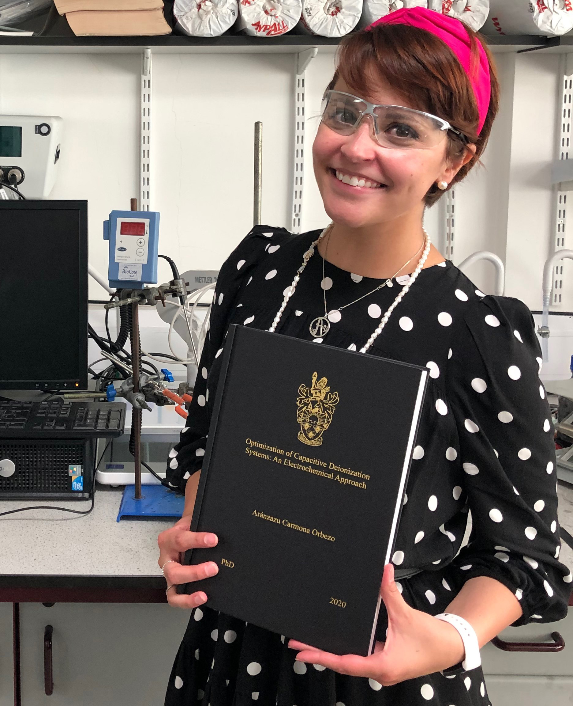 Aranza holding her completed PhD thesis
