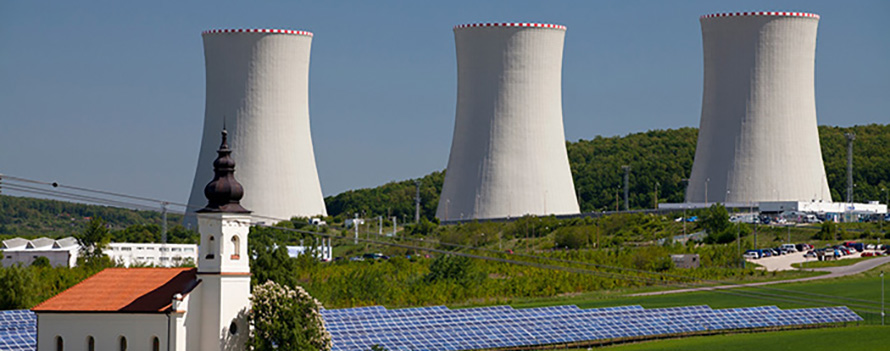 The water-cooling towers of the Mochovce nuclear power station in the Slovak Republic. A solar farm and a small church are in the foreground.