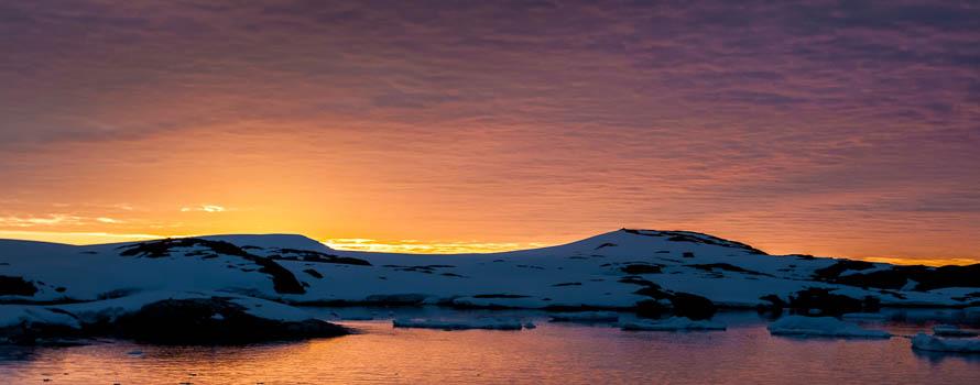 A photograph of the antarctic coast at sunset
