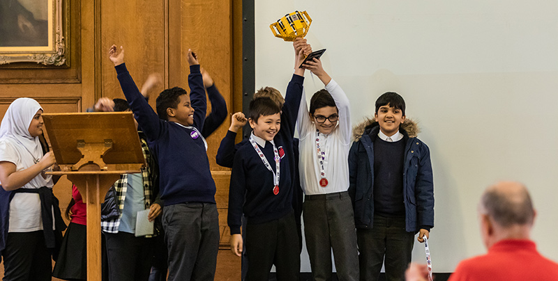 Victorious team holds aloft their trophy at FIRST LEGO League event