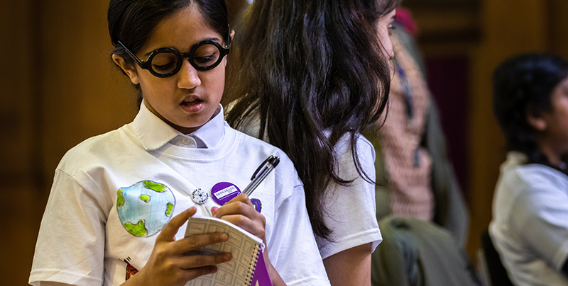 Girl taking notes at FIRST LEGO League event