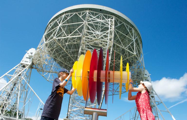 Children play in front of telescope