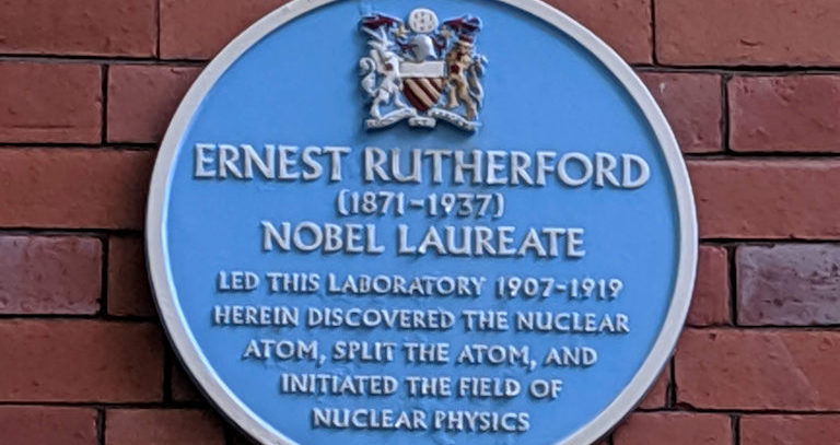 Blue plaque outside the Rutherford Building at The University of Manchester.