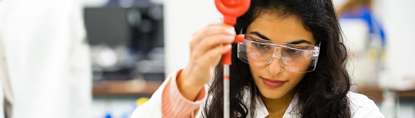 Scientist wearing protective glasses and holding a pipette