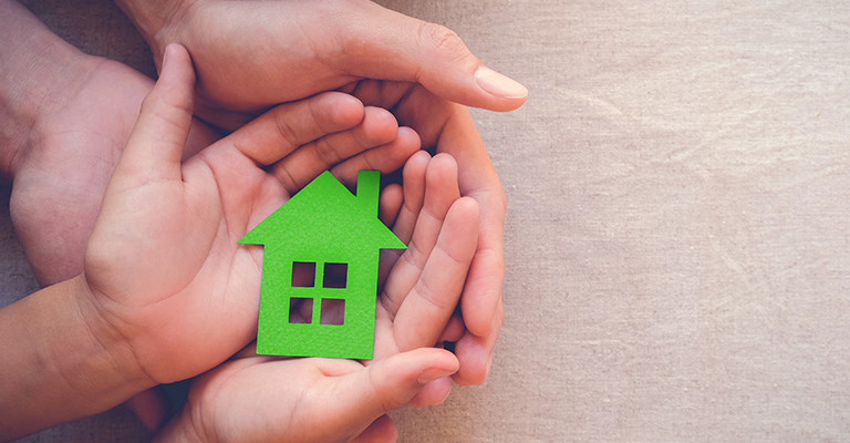 Small green house in adult and child's hands