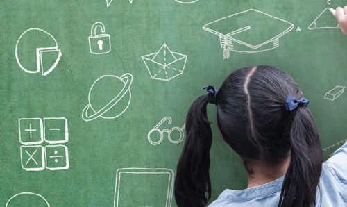 Young girl sketching on a blackboard