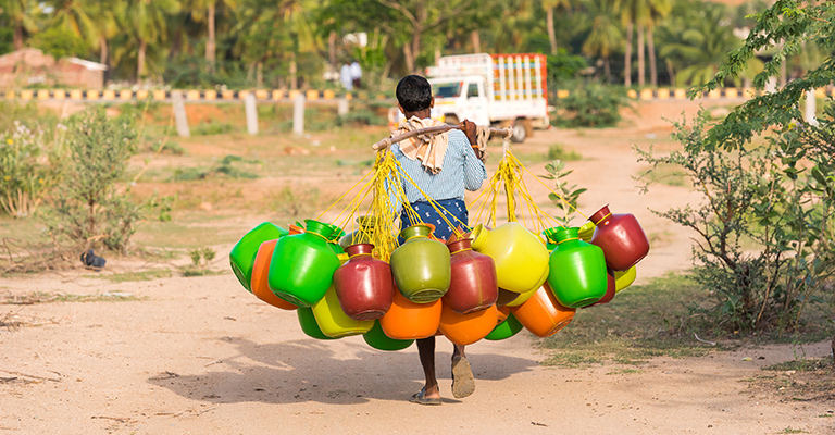 Man carrying colourful water tubs