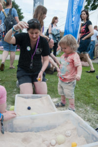 Sarah showing a child an experiment at Bluedot Festival
