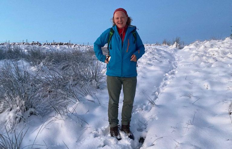 Katherine Morris stand on a snowy track and smiles at the camera.