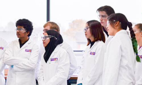 Chemistry students in lab coats and goggles