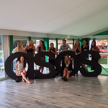 Ella and her team pose with the company's famous logo