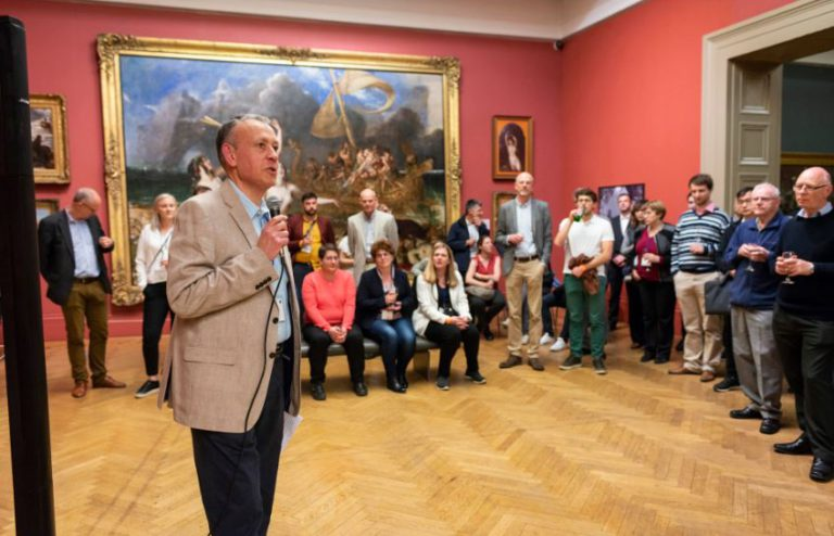 symposium speaker in art gallery