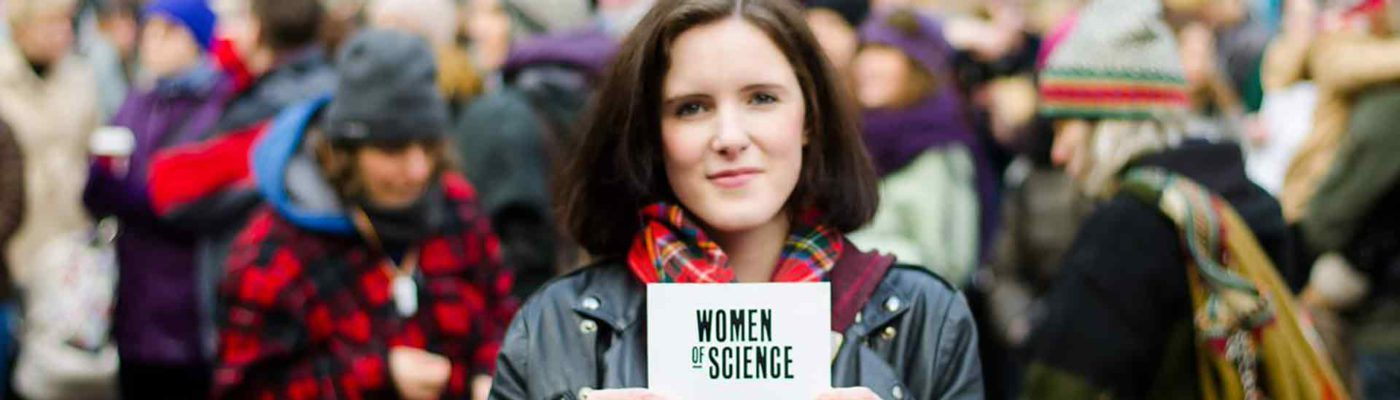 Woman holding up card that reads 'Women of Science'.